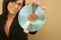 Woman shows the bottom of a DVD.